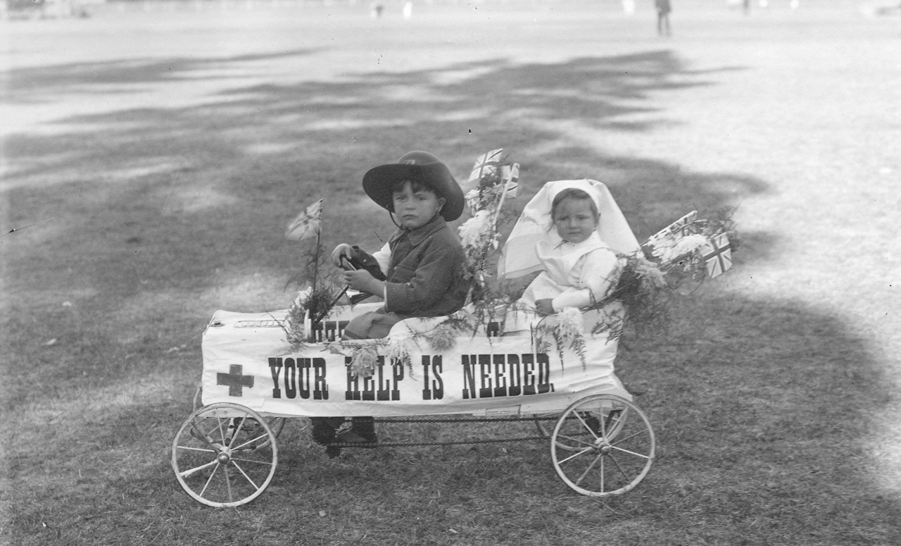 Two small children seated in a toy car [PRG 280/1/27/130]