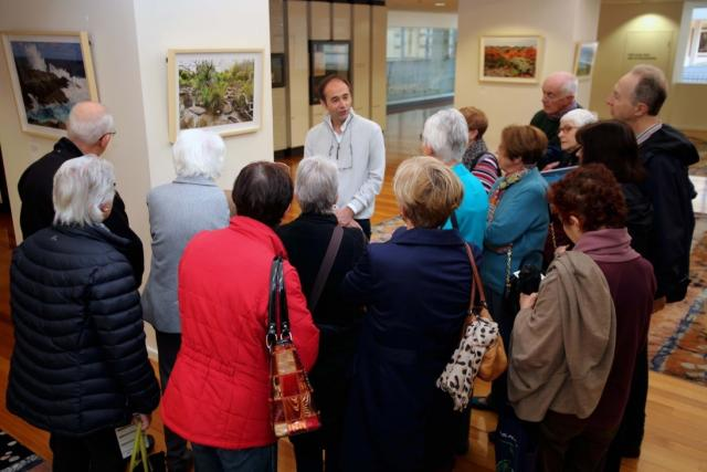 Federic Mouchet talking with a group of people at one of his exhibition tours.