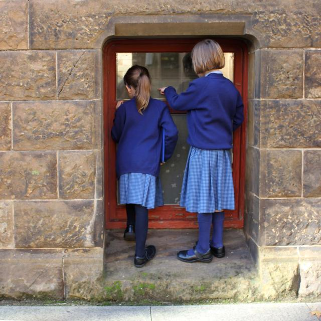 School kids looking in through a Mortlock basement window